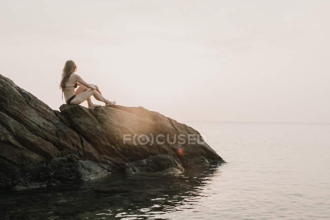 Жінка, стоячи на прибережні скелі — стокове фото