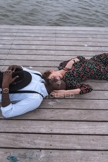 Couple lying on wooden pier — Stock Photo