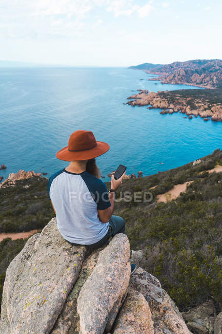 Man in hat sitting on rock at seaside — Stock Photo