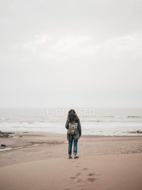 Woman with backpack at ocean — Stock Photo