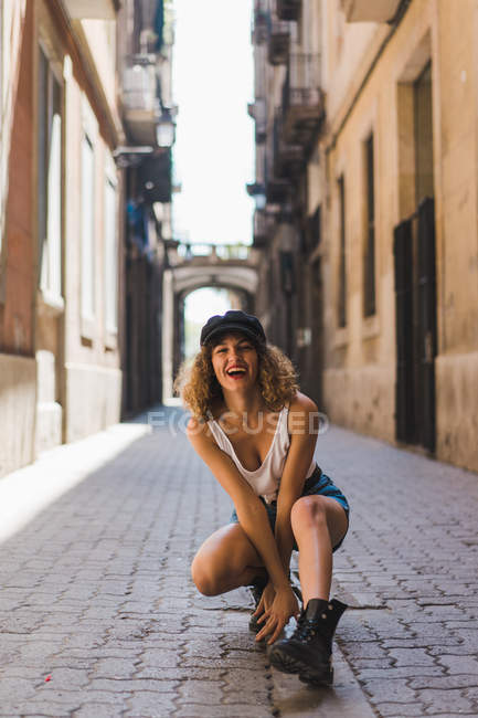 Woman in boots and cap sitting on street — Stock Photo