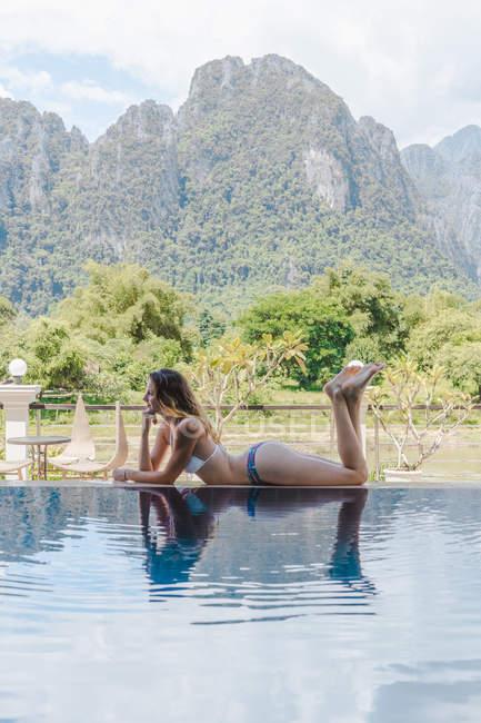 Mulher de biquíni deitada à beira da piscina — Fotografia de Stock