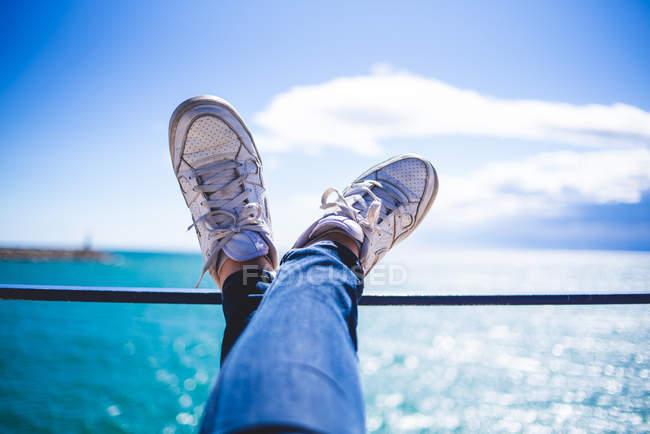 Jambes sur la main courante au bord de la mer — Photo de stock