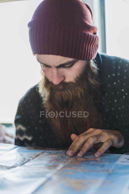 Hombre con barba mirando en el mapa - foto de stock