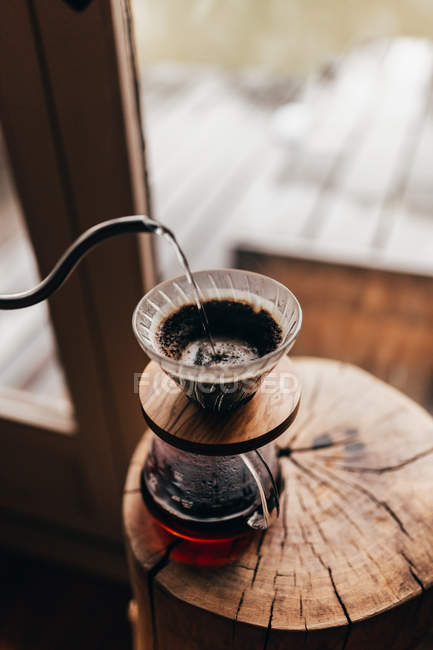 Pouring water in jug with coffee — Stock Photo