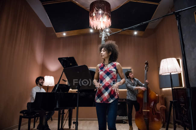 Woman singing on band rehearsal — Stock Photo