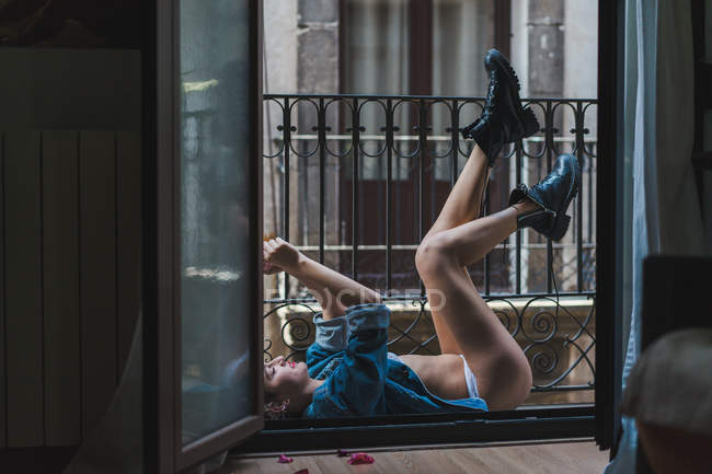 Frau liegend auf Balkon mit Beinen bis — Stockfoto