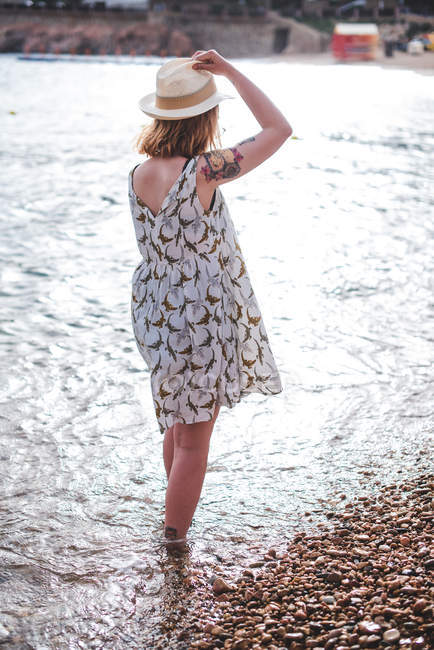 Woman standing in water on beach — Stock Photo