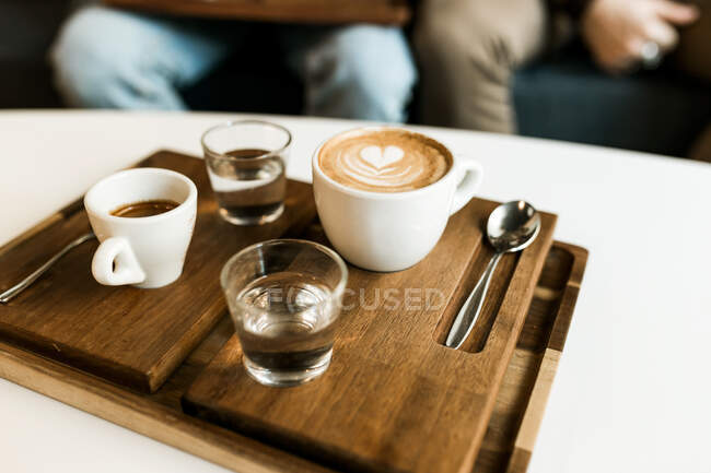Cups of espresso and latte served on wooden board on the table. — Stock Photo