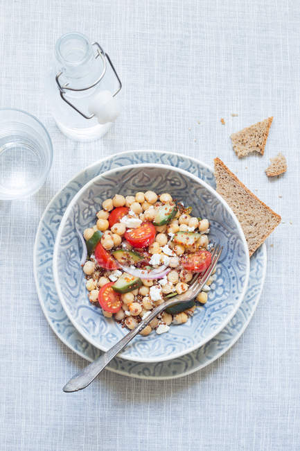 Top view of tasty chickpea vegetarian salad served with bread and water on table. — Stockfoto