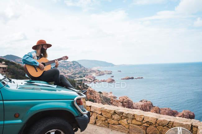 Uomo che suona la chitarra sul tetto dell'auto — Foto stock