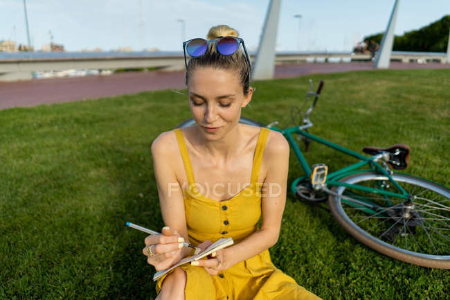 Mujer sentada sobre hierba con bicicleta - foto de stock