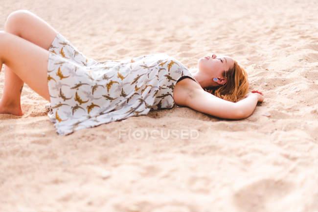 Mulher deitada na areia na praia — Fotografia de Stock