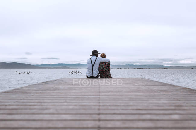 Couple sitting on wooden pier — Stock Photo