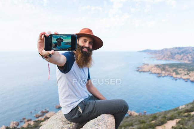 Homem alegre tomando selfie na rocha — Fotografia de Stock