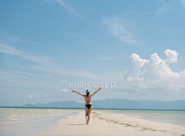 Donna a piedi sulla costa sabbiosa — Foto stock
