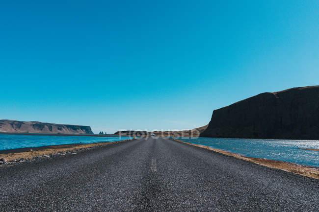 Асфальтована дорога через воду до гори — стокове фото