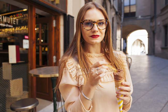 Stylish woman with ice cream standing on street and looking at camera — Stock Photo