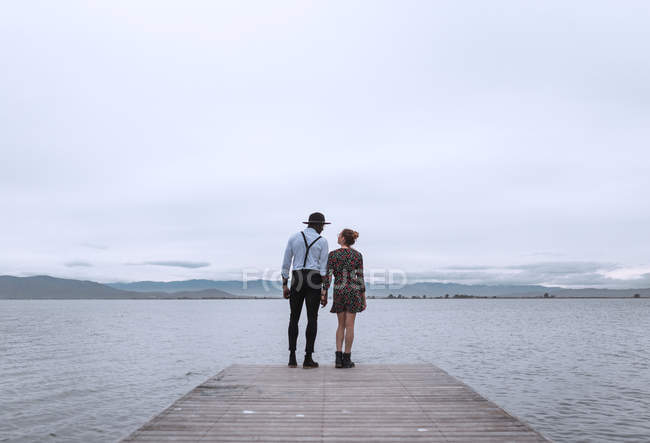 Couple standing on wooden pier — Stock Photo