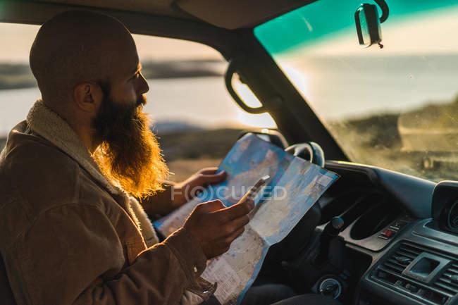 Hombre sentado en el coche y la celebración de mapa - foto de stock