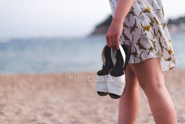 Femme portant des sandales sur la plage — Photo de stock