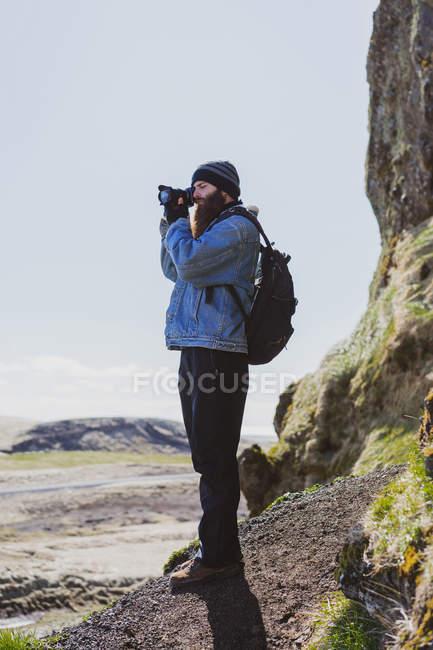 Hombre tomando fotos del paisaje de Islandia - foto de stock