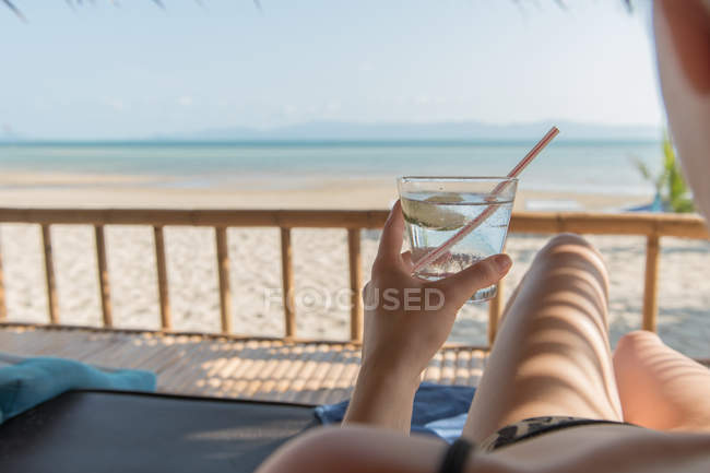 Woman with glass of water relaxing at seaside — Stock Photo