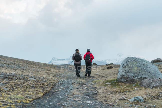Excursionistas caminando por sendero en pintoresco paisaje - foto de stock