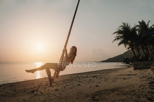 Frau schaukelt bei Sonnenuntergang am Strand — Stockfoto