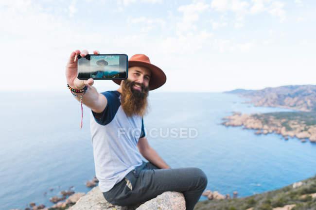 Веселый мужчина делает селфи на скале — стоковое фото