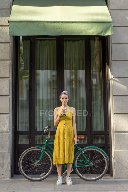 Woman standing with vintage bicycle on street — Stock Photo