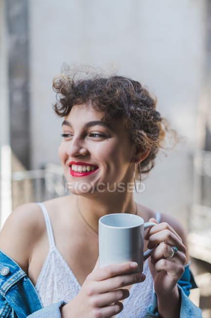 Фігурні жінка з чашкою кави на балконі — стокове фото
