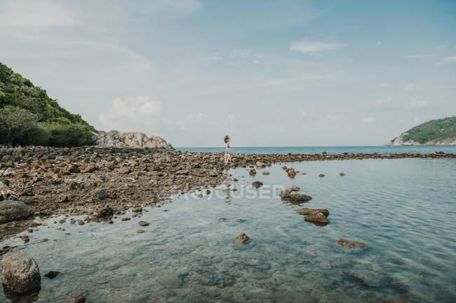 Жінка, стоячи на скелястий берег — стокове фото
