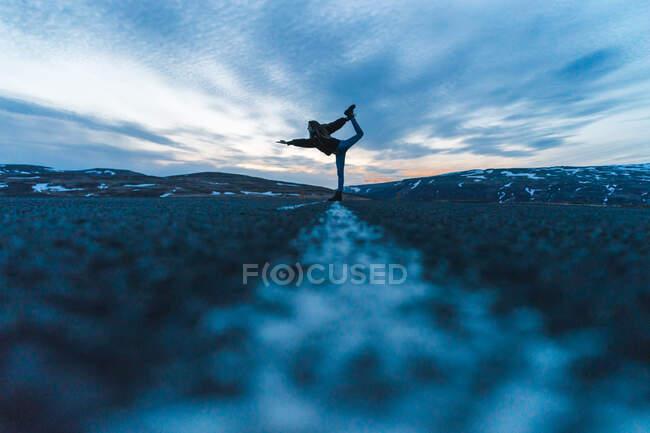 Бічний вид на молоду жінку, що стоїть посеред дороги в важкій позі і вказує наліво під час подорожі через Ісландію.. — стокове фото