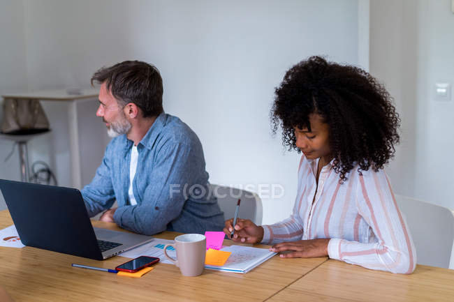 Woman sitting in office and writing in notebook — Stock Photo