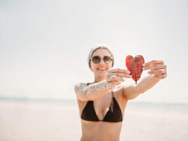 Donna con foglia a forma di cuore sulla spiaggia — Foto stock
