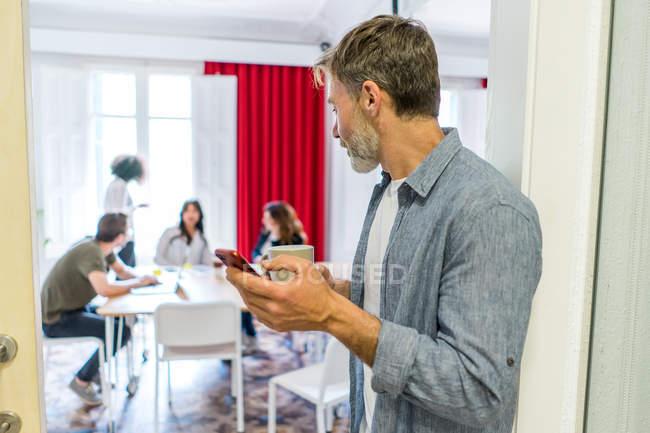 Uomo navigazione lo smartphone in ufficio — Foto stock