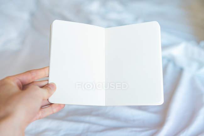 Bloco de notas vazio de exploração de mão — Fotografia de Stock