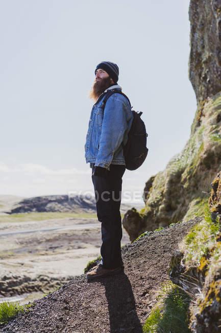 Homme debout de sac à dos à côté de la falaise — Photo de stock