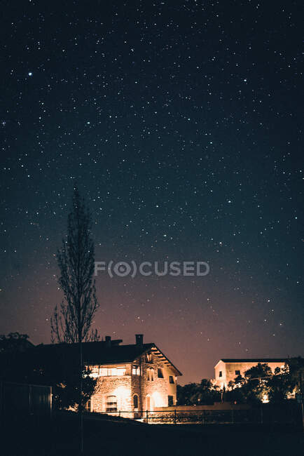 Stone houses illuminated with lamps in rural village under amazing sky with stars at night. — Stock Photo