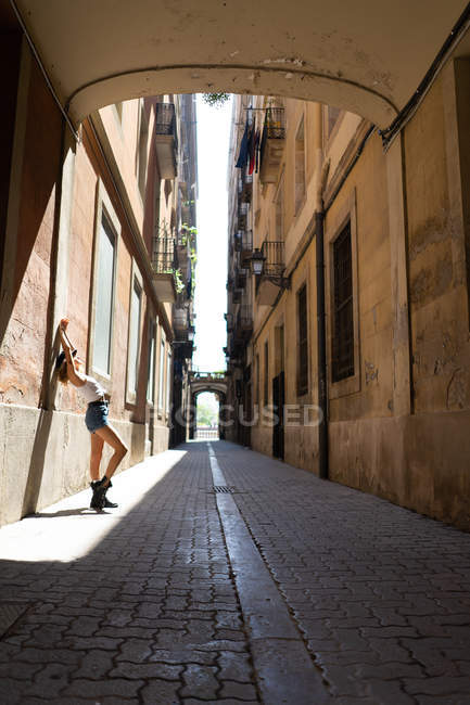 Woman leaning against wall on street — Stock Photo