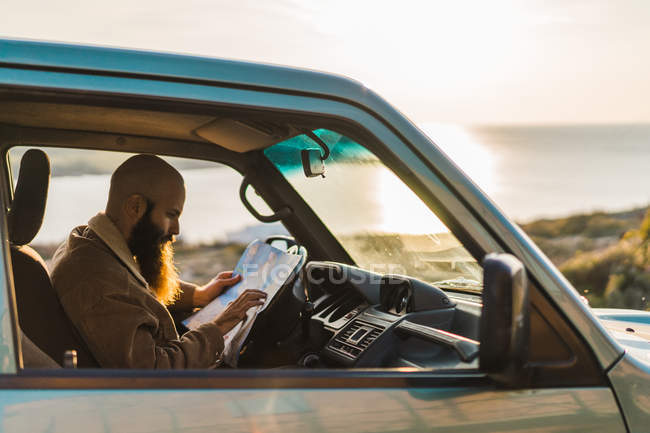 Man reading map in car — side view, Focus On Foreground