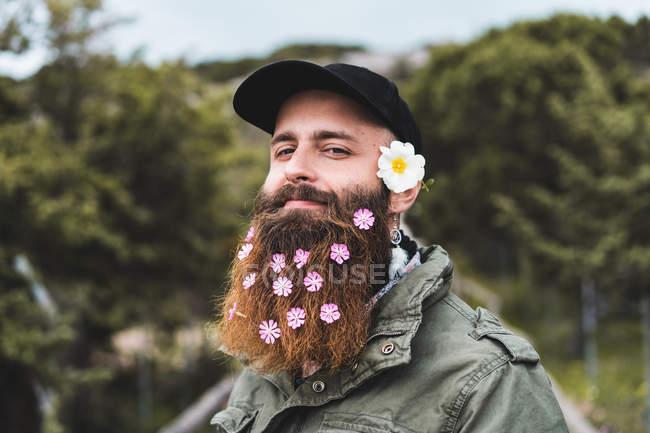 Человек с цветами в бороде — стоковое фото