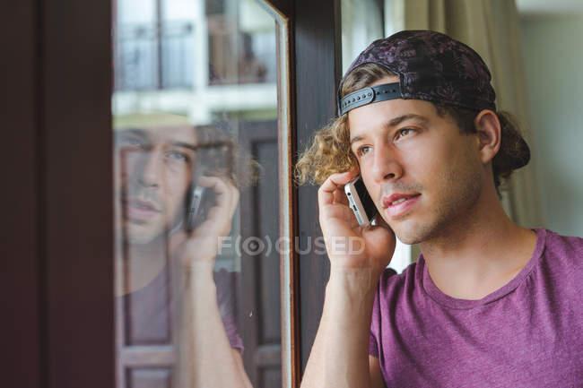 Homem falando no telefone celular na janela — Fotografia de Stock