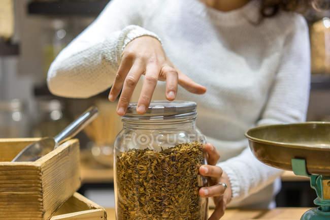 Жінка відкриття jar з спецій — стокове фото