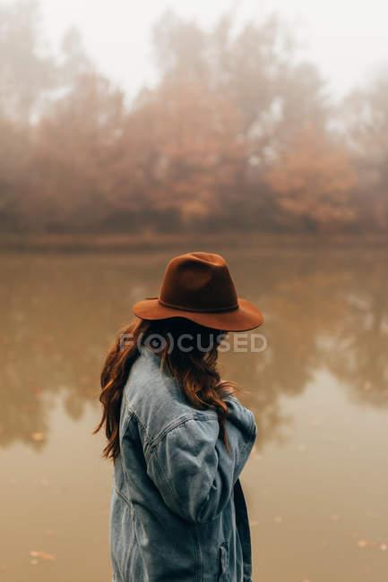 Жінка носить капелюх стоячи на ставок — стокове фото