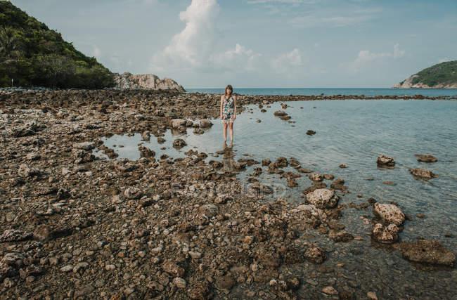 Жінка, стоячи на скелястий берег в океані — стокове фото