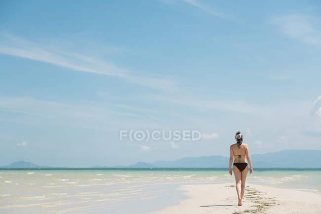 Жінка вигулює на піщаному узбережжі — стокове фото
