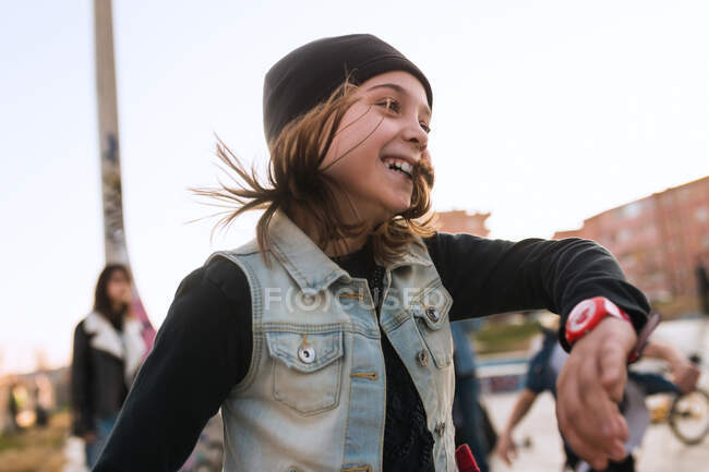 Little stylish girl laughing and showing dance having fun with friends on street. — Stock Photo