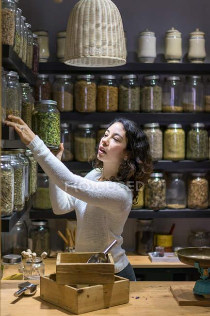 Женщина берет банку со специями — стоковое фото